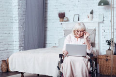 Involved handicap aging woman using laptop at home. Enjoying modern technologies. Concentrated elderly enable woman sitting in the wheelchair at home while stock photo