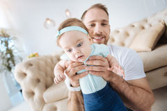 Involved little kid in the arms of the father at home Stock Images