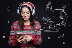 Involved pleasant woman listening to the Christmas songs. Enjoying jingle bells song. Cheerful amused young woman standing against imaginary drawing on the black Royalty Free Stock Photography