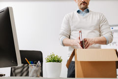 Involved staff member packing the box and leaving the office. Searching the solution . Fired involved depressed employee standing and packing the box with his Stock Image