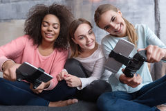 Involved young girls playing game consoles Stock Image