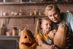 Involverad dotter som förbereder en pumpa för allhelgonaafton med hennes moder royaltyfria foton