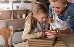 Involverad liten flickamatlagning med hennes moder i köket royaltyfria bilder