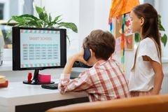 Involverade klasskompisar som sitter bredvid datoren royaltyfria bilder