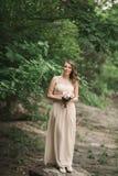 Inwedding klänning för härlig lyxig ung brud som står den near floden med berg på bakgrund Royaltyfria Bilder