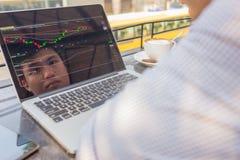 Inwestor ogląda zmianę rynek papierów wartościowych na laptopie obraz royalty free