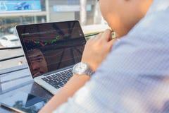 Inwestor ogląda zmianę rynek papierów wartościowych na laptopie zdjęcie stock