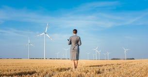 Inwestor w zielony energetycznym patrzejący jej silniki wiatrowych zdjęcia stock