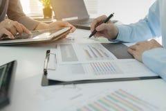 Inwestora kierownictwo dyskutuje planu wykresu pieniężnych dane na biuro stole z laptopem i pastylką fotografia stock