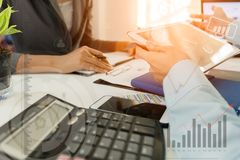Inwestora kierownictwo dyskutuje planu wykresu pieniężnych dane na biuro stole z laptopem i pastylką fotografia royalty free