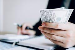 Inwestorzy kalkulują na kalkulatorów inwestorskich kosztach i trzymają gotówkowe notatki w ręce obrazy stock