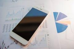 Inwestycja w ochronach, pojęcie Mobilni zastosowania dla finansistów Smartphone na tle pieniężni raporty zdjęcia stock