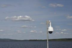 Inwigilaci kamera z niebieskim niebem z chmurami i jezioro w półdupkach Obrazy Stock