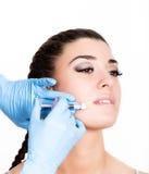 Inyección de la belleza del doctor en guantes azules Mujer joven en salón de belleza