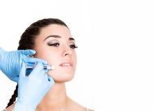 Inyección de la belleza del doctor en guantes azules Mujer joven en salón de belleza Espacio libre para el texto