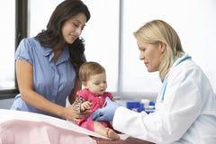 Inyección del bebé del doctor In Surgery Giving Fotografía de archivo libre de regalías