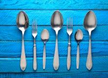 Inzameling van lepels en vorken op een blauwe houten achtergrond Stock Afbeeldingen
