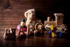 Inzameling van oud houten kinderenspeelgoed met teddybeer stock fotografie
