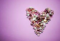 Inzameling van Roze die glasparels in een hart worden gevormd stock foto