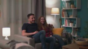 Inzoomen geschoten paar die op een komedie in de woonkamer in de avond letten stock video