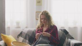Inzoomen van vrouwenzitting op laag en het breien in huis en het kijken in camera stock video