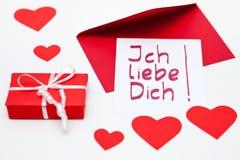 Io-lovey-voi-nota in tedesco per il giorno del ` s del biglietto di S. Valentino e un pacchetto rosso Immagine Stock