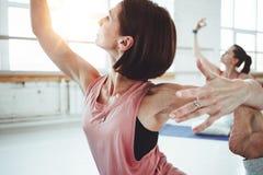 A ioga apta forte do treinamento da mulher levanta na esteira da aptidão junto com o grupo de pessoas no fundo Cuidado e estilo d imagem de stock royalty free