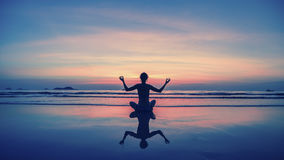 Ioga, aptidão, estilo de vida saudável Mostre em silhueta a menina da meditação no fundo do mar e do por do sol impressionantes Imagem de Stock