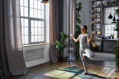 Ioga avançada praticando da mulher na sala de visitas em casa Uma série de poses da ioga Fotos de Stock