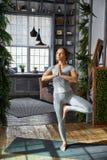 Ioga avançada praticando da mulher na sala de visitas em casa Uma série de poses da ioga Imagem de Stock
