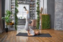 Ioga avançada praticando da mulher na sala de visitas em casa Uma série de poses da ioga Imagens de Stock