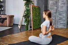 Ioga avançada praticando da mulher na sala de visitas em casa Uma série de poses da ioga Imagem de Stock Royalty Free