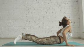 Ioga bonita nova que levanta em um fundo branco da parede de tijolo, estilo de vida saudável filme