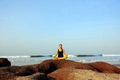 Ioga da jovem mulher bonita e exercícios praticando do esticão na praia do oceano do verão foto de stock royalty free