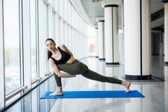 a ioga da jovem mulher faz exercícios no salão grande com as janelas panorâmicos grandes Imagens de Stock