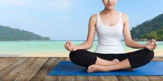 Ioga da meditação das mulheres na praia de madeira do balcão fotos de stock