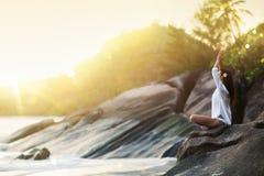 A ioga da mulher medita sobre uma rocha na praia do oceano imagens de stock royalty free