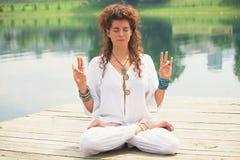 Ioga da prática da jovem mulher exterior pelo lago Imagem de Stock Royalty Free