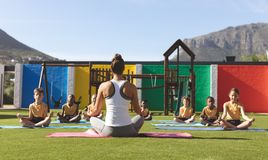 Ioga de ensino do professor da ioga aos estudantes no campo de jogos da escola foto de stock