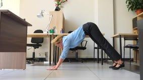 Ioga de execução executiva fêmea em seu local de trabalho no escritório 4k, movimento lento video estoque