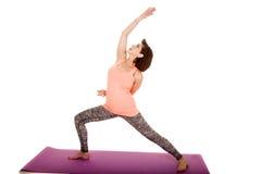 A ioga de uma mulher mais idosa investe contra o braço acima fotografia de stock