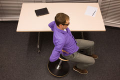 Ioga do escritório - homem de negócio que exercita na mesa Imagem de Stock