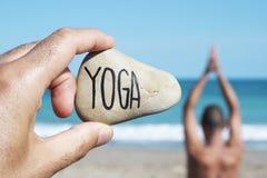 Ioga do homem e do texto do iogue em uma pedra Foto de Stock