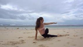 Ioga do treinamento da mulher na praia video estoque