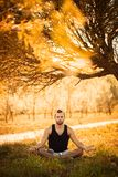 Ioga e conceito saudável do estilo de vida Retrato do homem que medita na pose fácil do assento na grama no parque Alargamento br imagem de stock royalty free
