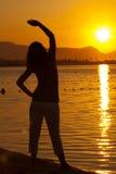 Ioga excercising da mulher durante o por do sol fotos de stock