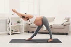 Ioga feliz do treinamento da mulher gravida em casa Imagens de Stock