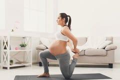 Ioga feliz do treinamento da mulher gravida em casa Fotografia de Stock