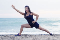 Ioga indo da jovem mulher na praia Imagem de Stock Royalty Free