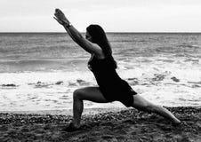 Ioga indo da jovem mulher na praia no amanhecer Fotos de Stock